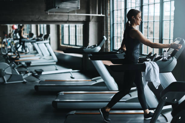 Using a machine to become one Shot of an attractive young woman working out on a treadmill in a gym cardiovascular exercise stock pictures, royalty-free photos & images