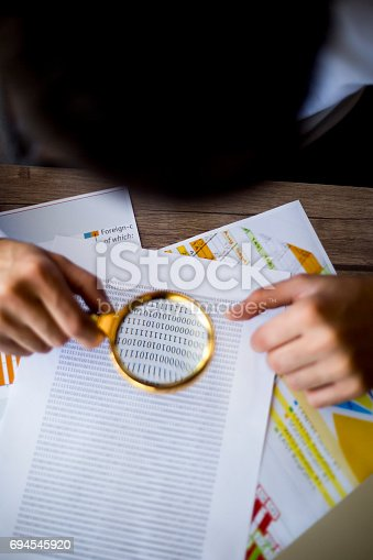 istock Using a magnifying glass 694545920