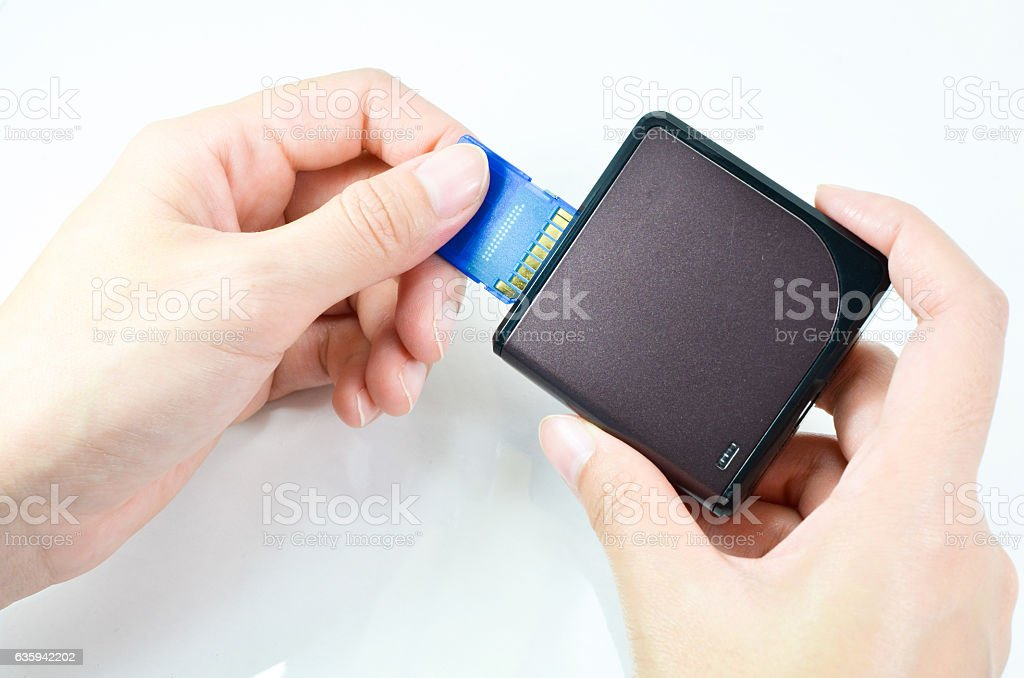 Using a memory card reader on white background stock photo