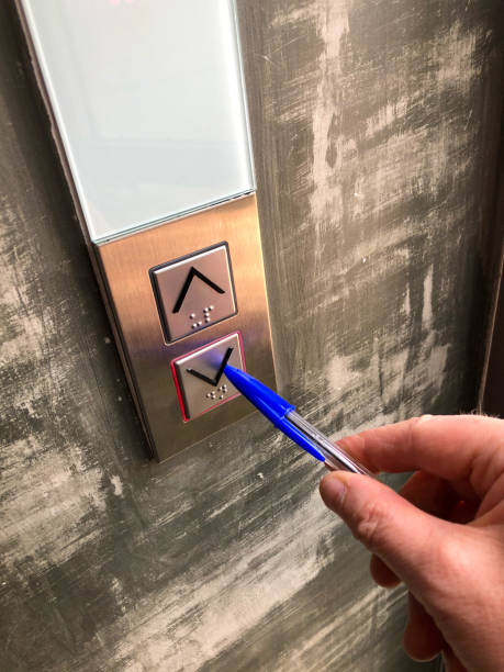 Using a pen to press an elevator down button Someone using a blue lidded plastic pen to press the external braille down button on a hotel elevator, during a holiday abroad. It is being pressed in this way to avoid physical finger contact during the global Coronavirus scare which is breaking out around the world. avoidance stock pictures, royalty-free photos & images