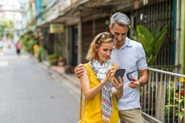 Using a Phone While Street Market Shopping in South East Asia Mature couple using a mobile smart phone to look for information market area of Bangkok while on vacation in South East Asia shopping couple asian stock pictures, royalty-free photos & images