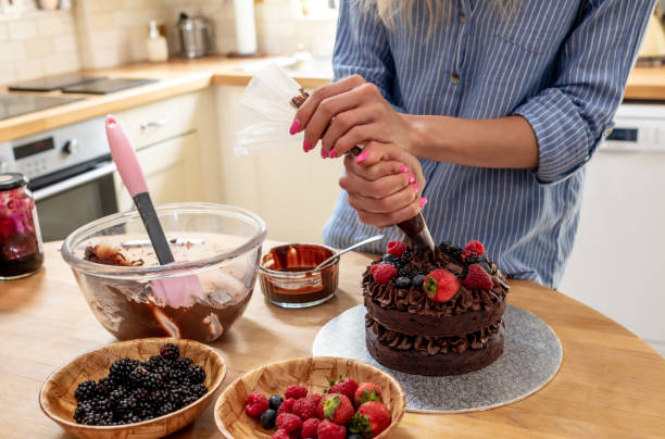 Using a piping bag to pipe chocolate icing on to a cake stock photo