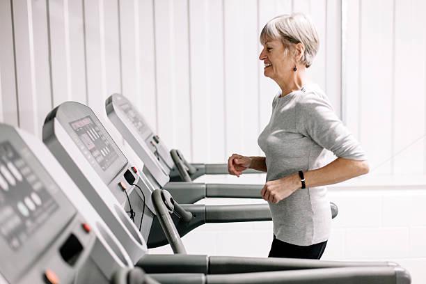 Using a running machine; beautiful, senior woman stock photo