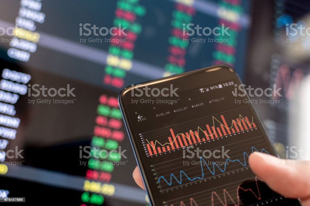 Using a smartphone and PC to look at financial data stock photo