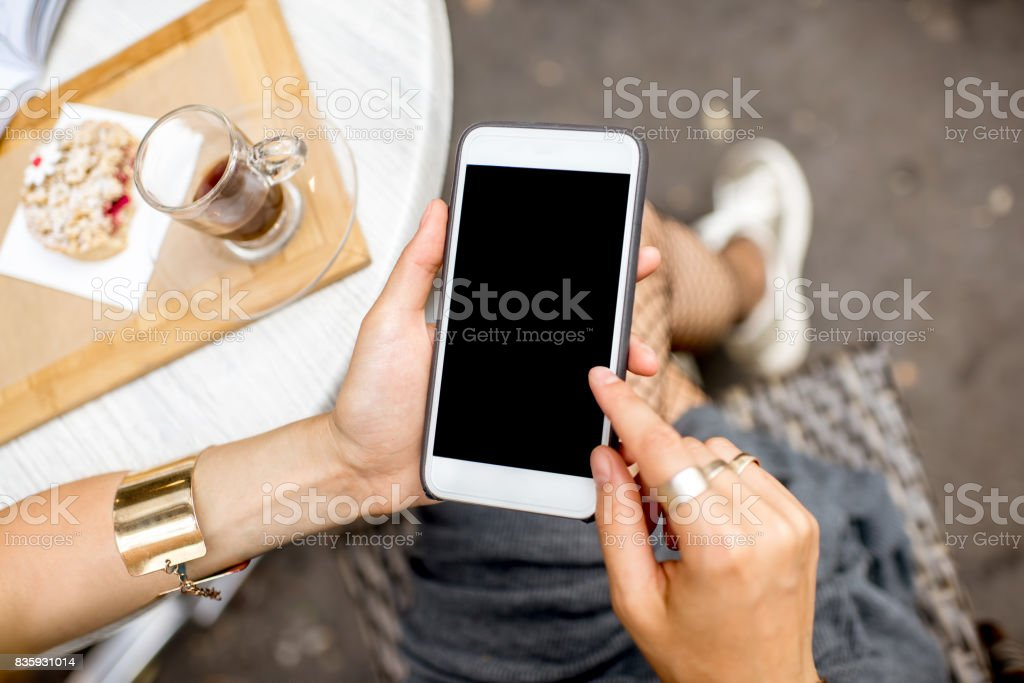 Using a smartphone at the cafe stock photo