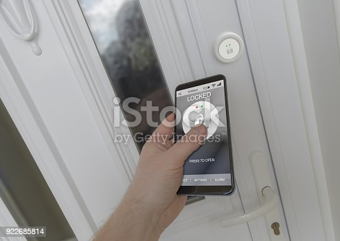 istock Using a smartphone to open an electronic lock on a front door 922685814