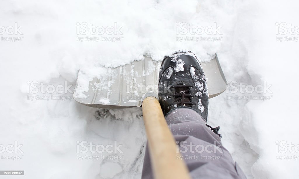 Using a snow shovel in a snowed yard stock photo