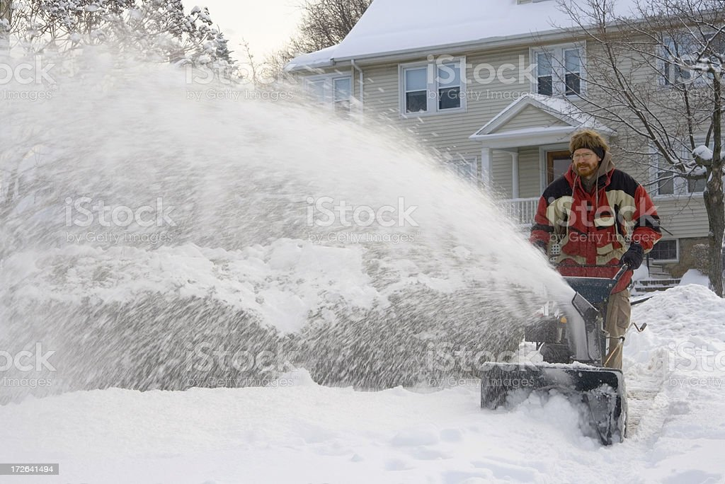 Using a snowblower to clear the sidewalk stock photo