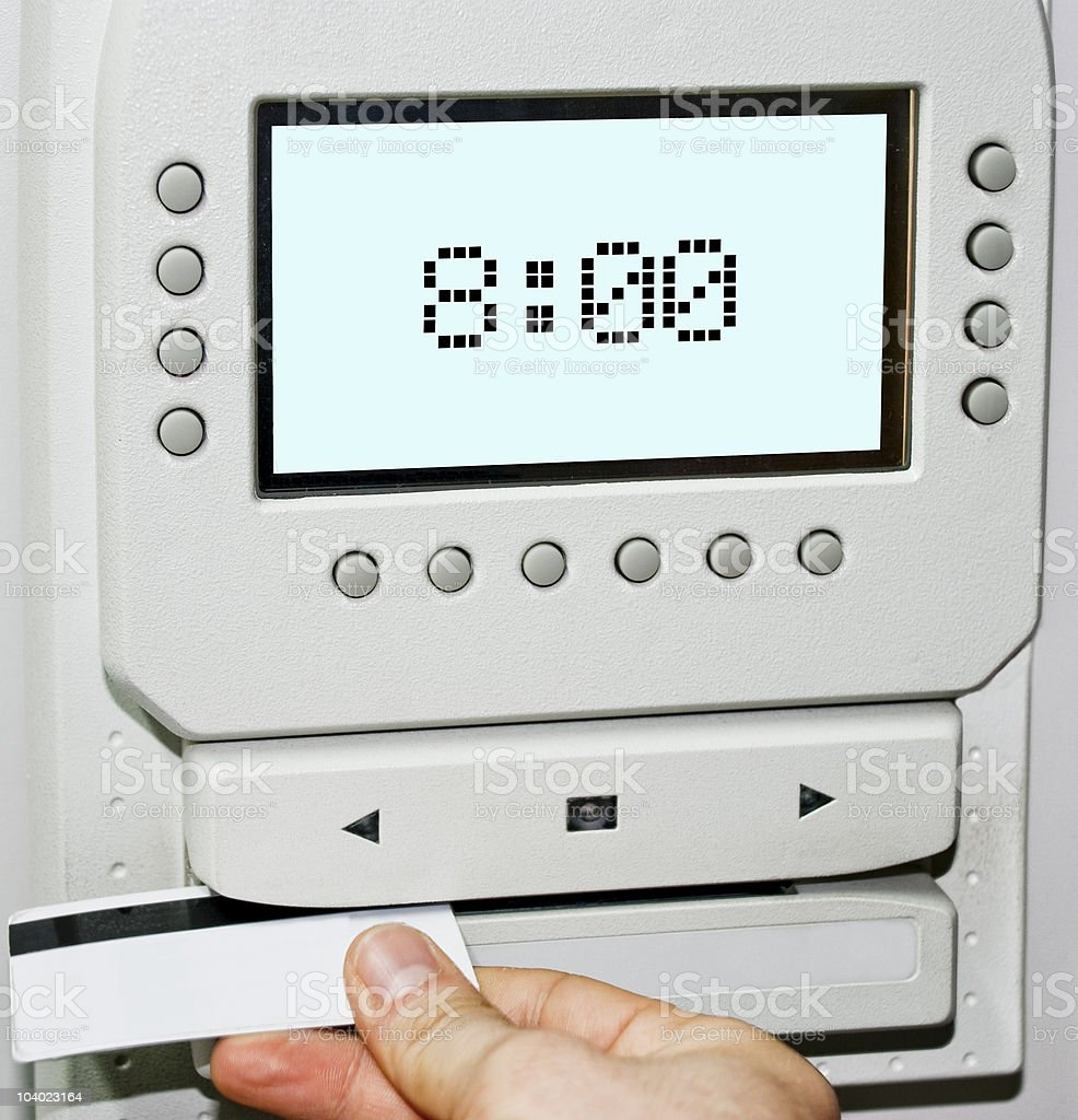 Using a time card to clock in at a work computer stock photo