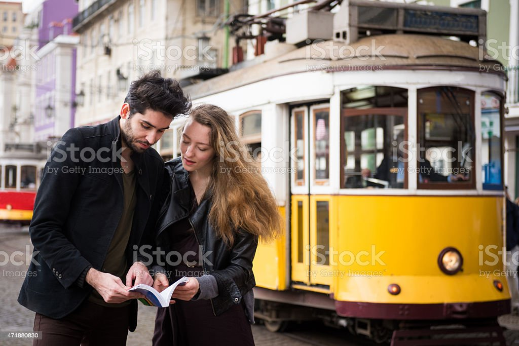 Couple looking at a travel guide book on a European vacation