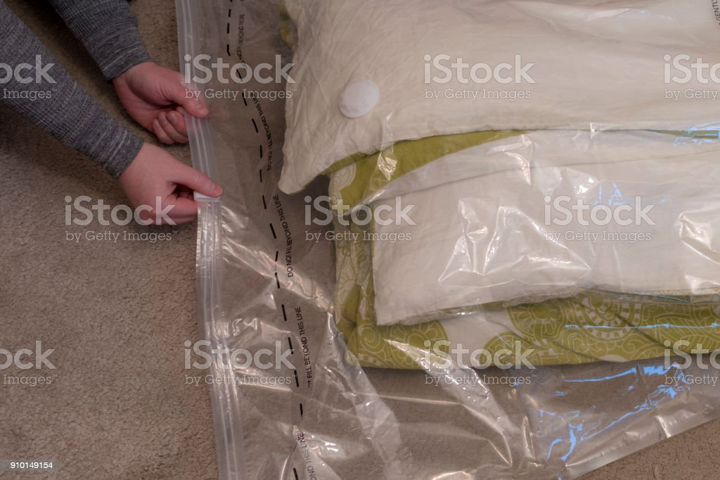 Using a vacuum storage bag to remove air from duvet