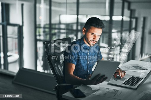 Cropped shot of a handsome young businessman working late at night at his desk in the office