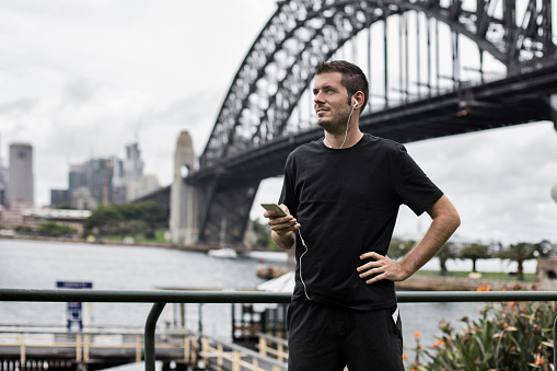 Young man using a mobile phone application for the running at Sydney - Australia.