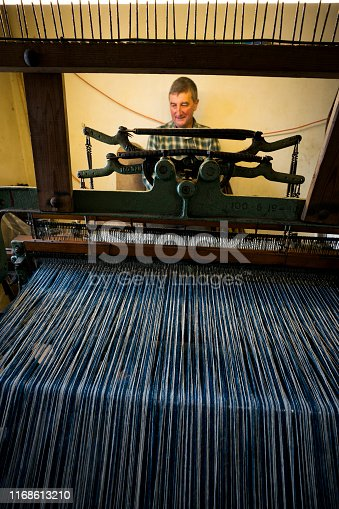 A male crofter busy at work on an older, smaller Hattersley foot-powered loom at home weaves wool sheared, dyed and spun on the island according to Parliment bylaws to create distinctive tweed cloth fabric on the Isle of Lewis, Outer Hebrides, Scotland, UK