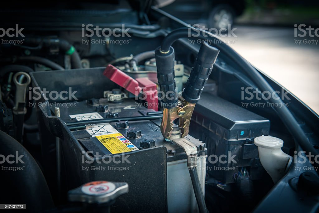 Using battery jumper cables to charge battery stock photo