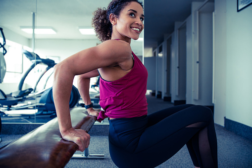 Female working out at the gym, doing triceps exercises off a bench