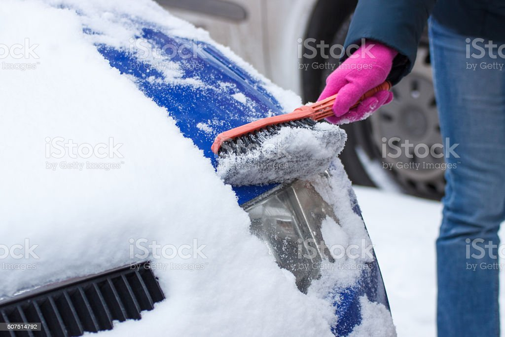 Using brush and remove snow from car and headlight stock photo
