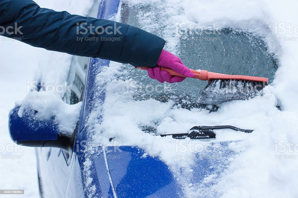 Using brush and remove snow from car and windscreen stock photo