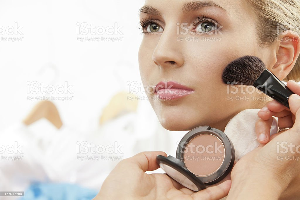 Using brush to apply blush on cheeks royalty-free stock photo
