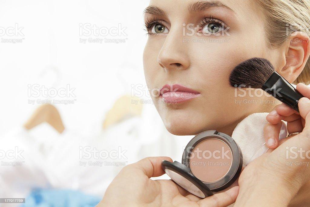 Using brush to apply blush on cheeks stock photo