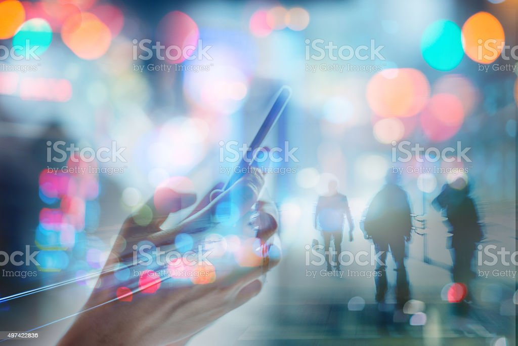 using cell phone in city abstract stock photo