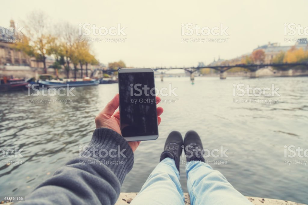 Using cellphone near the river Seine in Paris. stock photo