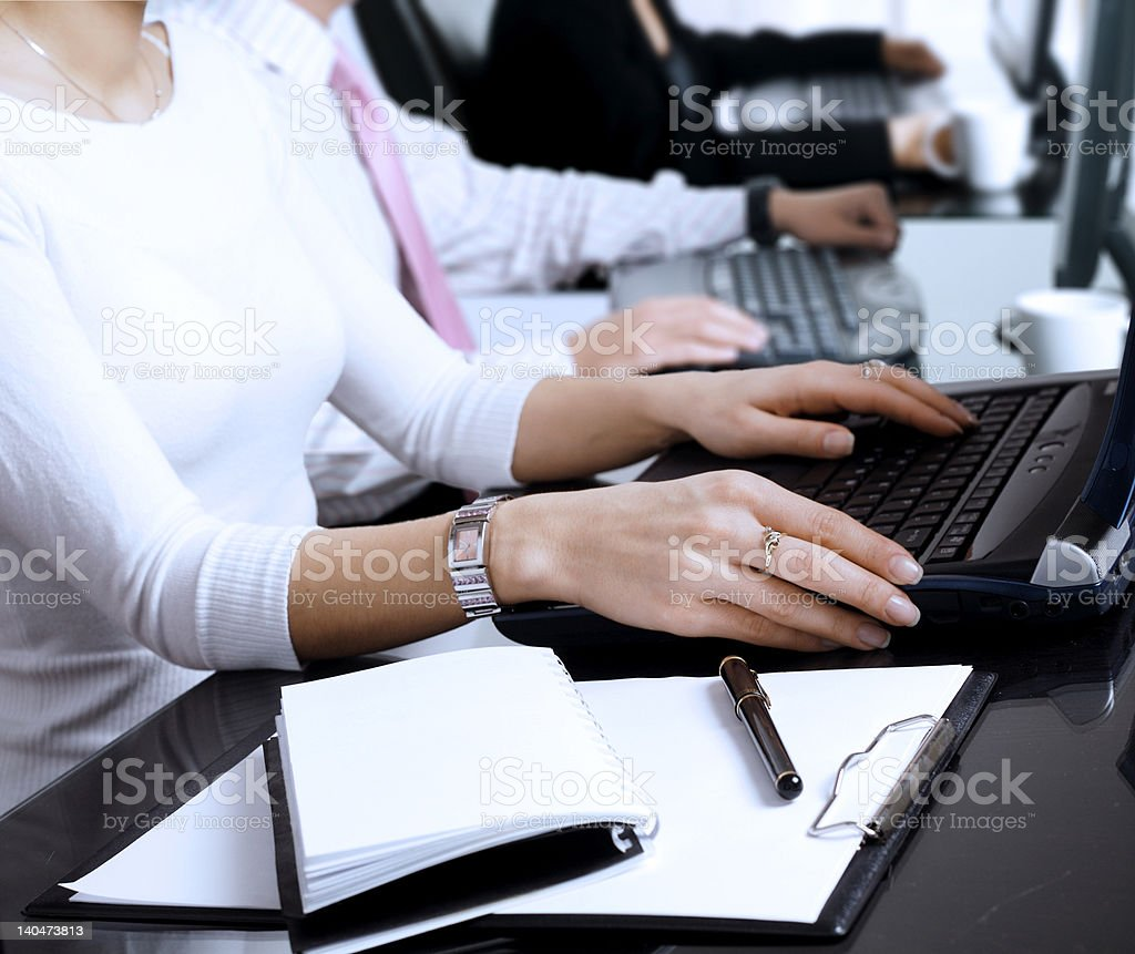 Using computer Close-up os human hands. Young office workers are typing on keyboards in front of their office computers. Business Stock Photo