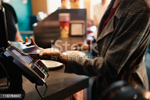 Close-up of a unrecognisable person using their smart phone to pay by contactless.