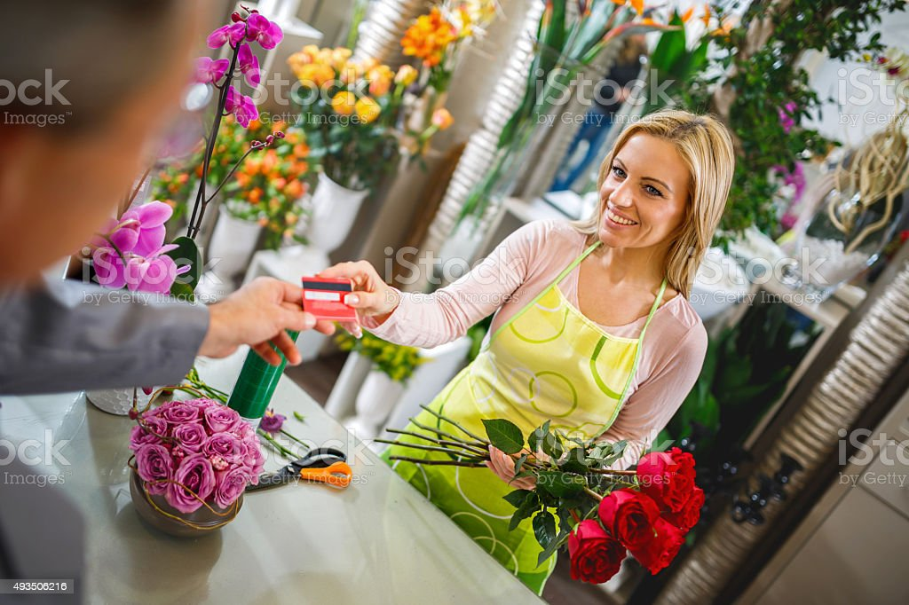 Smiling florist taking credit card from a customer and selling...