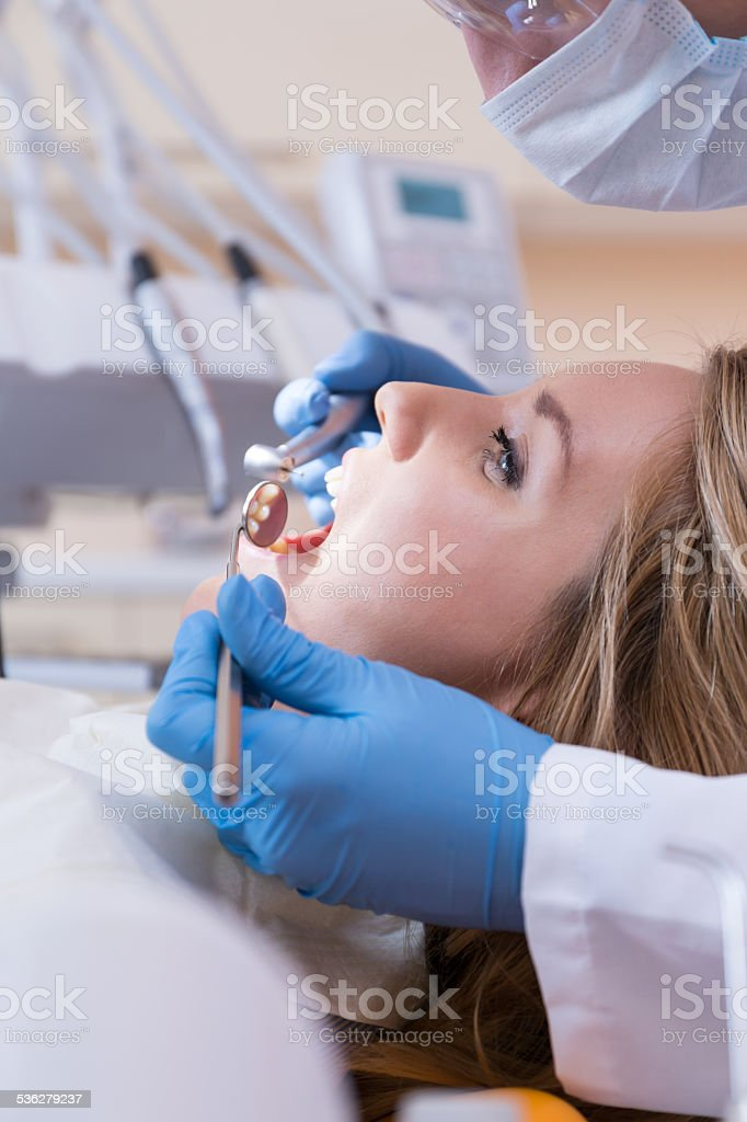 Using dental drill and mouth mirror stock photo