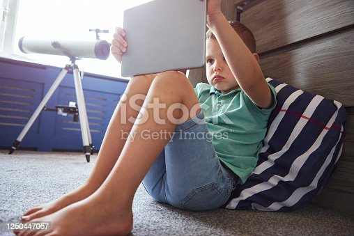A young boy sat in his bedroom reading or watching a video on his digital tablet