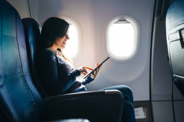 Using digital tablet on an airplane stock photo