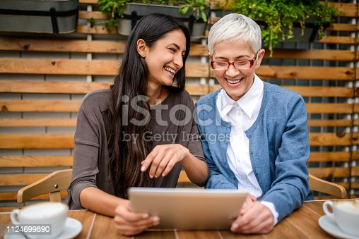 Two happy smiling women using digital tablet at the bar