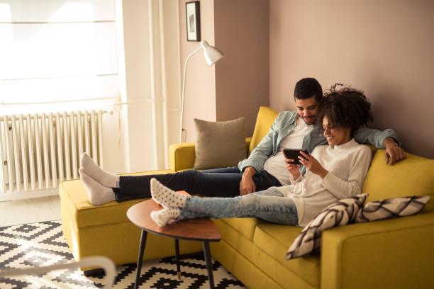 digitalen tabletts - lässiges wohnzimmer stock-fotos und bilder