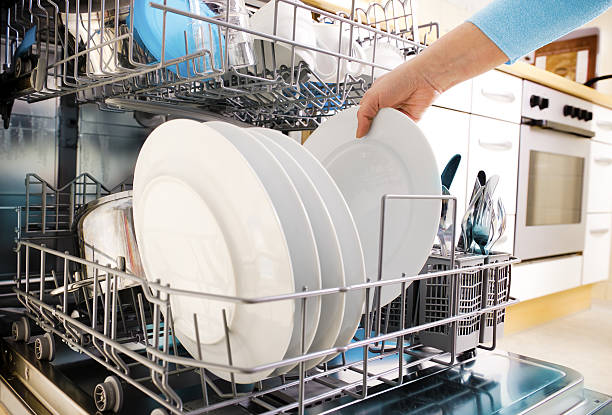 using dishwasher close-up of female hands loading dishes to the dishwasher dishwasher stock pictures, royalty-free photos & images