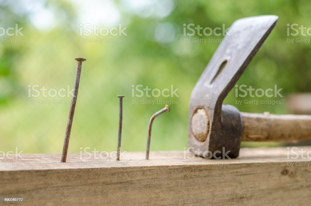 Using hammer and nails and curved nail on wood and bokeh background stock photo