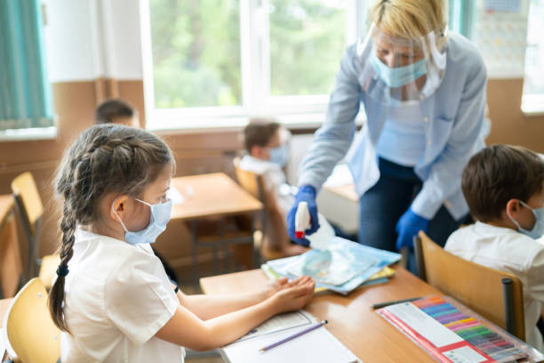 COVID-19. Using hand sanitizer in the classroom Service staff disinfecting hands of a girl in the classroom school building stock pictures, royalty-free photos & images