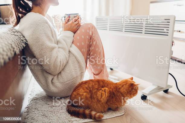 Using heater at home in winter woman warming and drinking tea with picture id1098335004?b=1&k=6&m=1098335004&s=612x612&h=iwwuf3eingtopn iocyslg2rpl168w0g38m9a5zp9ae=