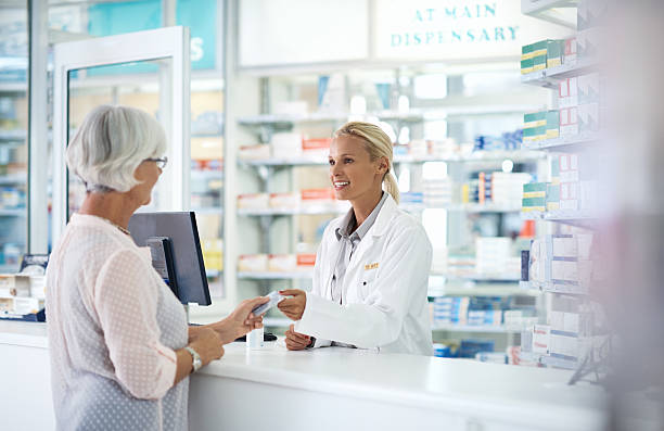 using her senior citizen's discount for her monthly medication - chemist stock photos and pictures