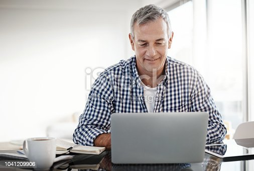 Shot of a mature man working on a laptop at home