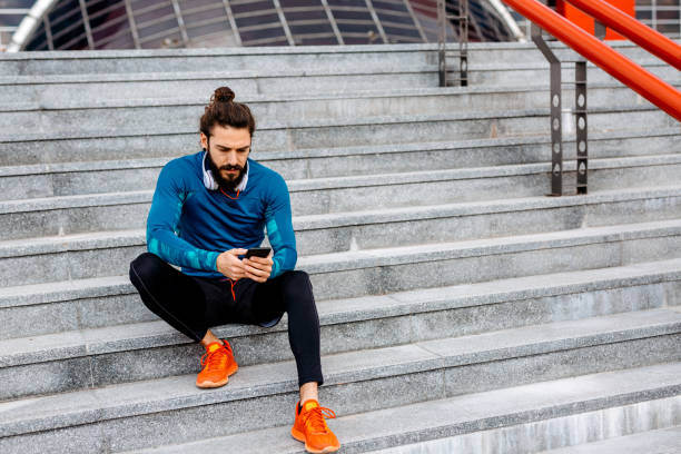 using his smartphone after running - milan2099 stock photos and pictures