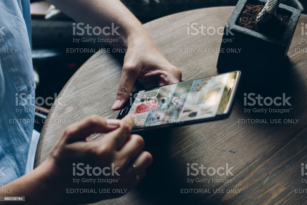 Using Instagram application Moscow, RUSSIA - August 20th, 2017: Young woman holding smartphone with search page screen of Instagram application. Instagram is largest and most popular photograph social networking. Applying Stock Photo