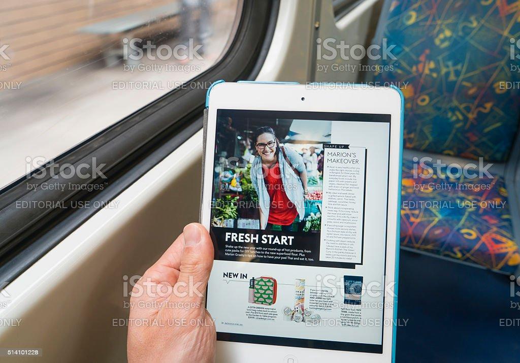 Using iPad on train during commuting stock photo