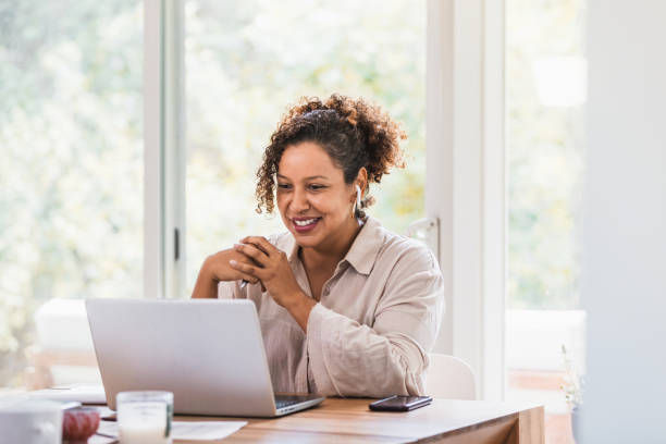Using laptop and bluetooth earbuds, woman video conferences from home stock photo