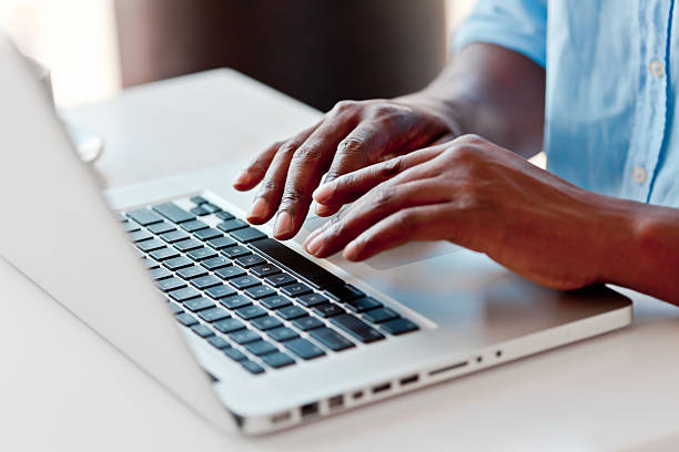 Using laptop Close-up on male hands typing on laptop keyboard. computer keyboard stock pictures, royalty-free photos & images