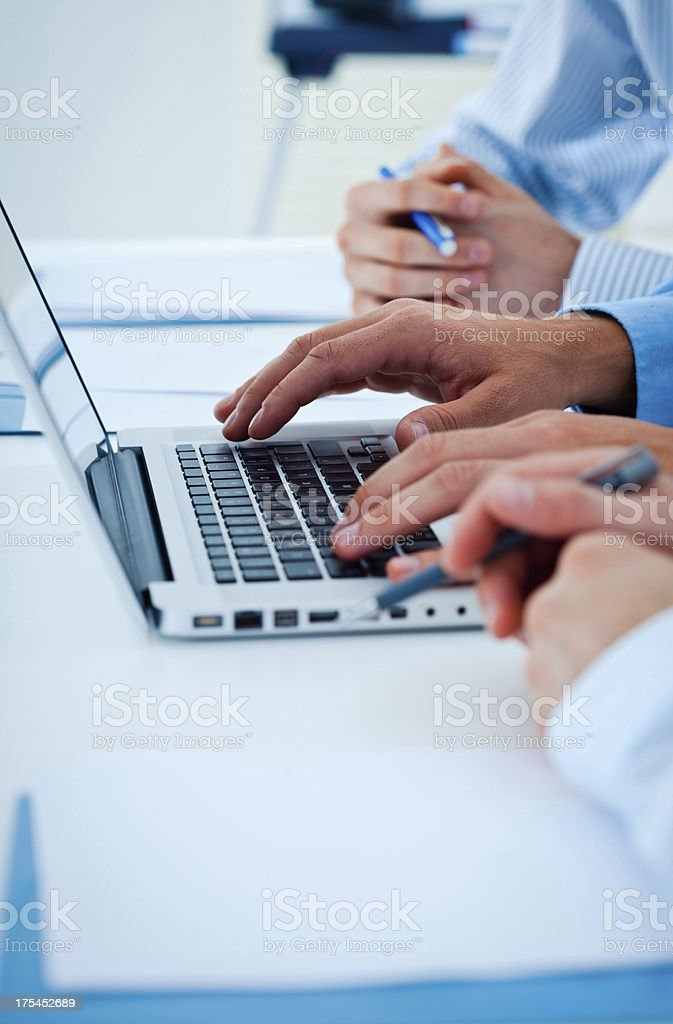 Using laptop Close-up on businessman's hands using laptop during business meeting. Adult Stock Photo