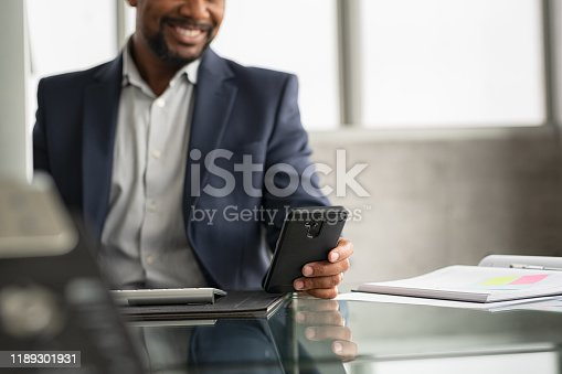 Detail of black manager in suit sending phone message in a modern office. Closeup of african businessman hand checking cellphone. Smiling mature man using smartphone while working on desk at modern office.