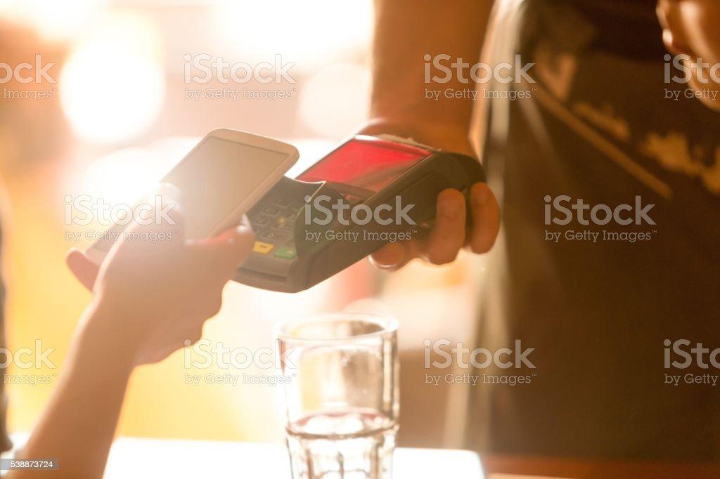 Mit Mobiltelefon für kontaktloses Bezahlen – Foto