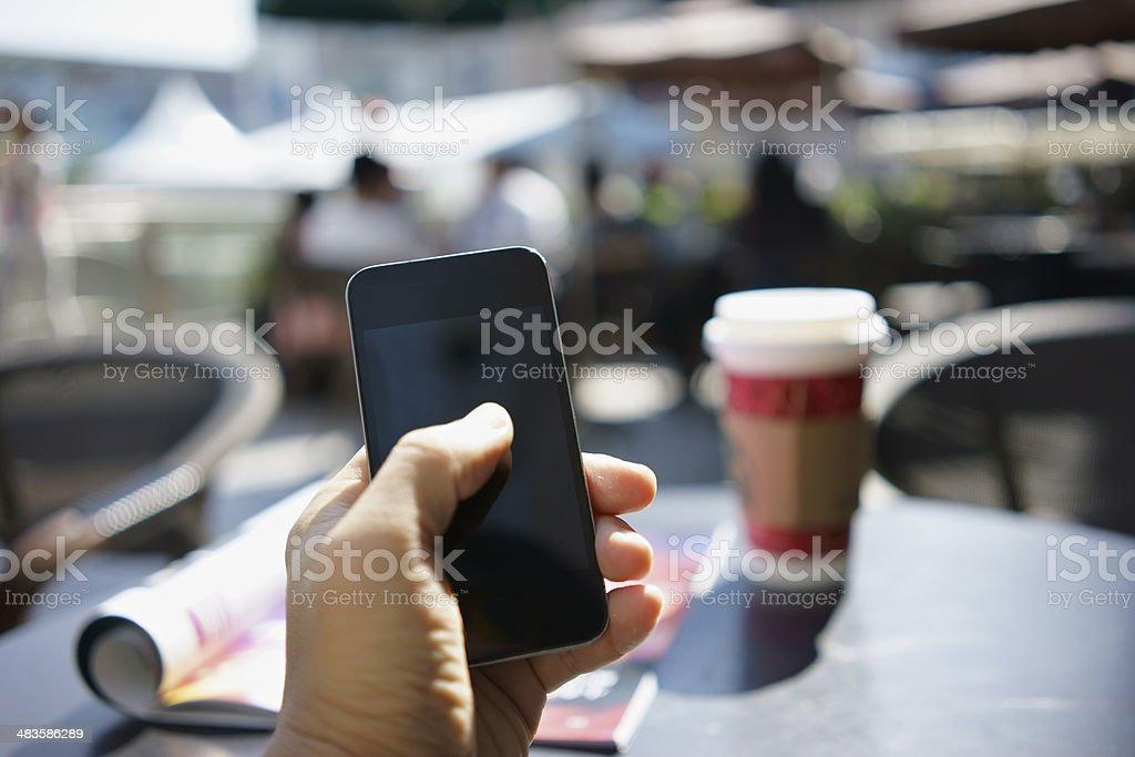 using mobile phone in a cafe stock photo