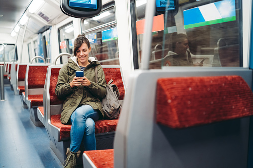 Young, smiling, woman using mobile phone on a metro ride. Hamburg, Germany.